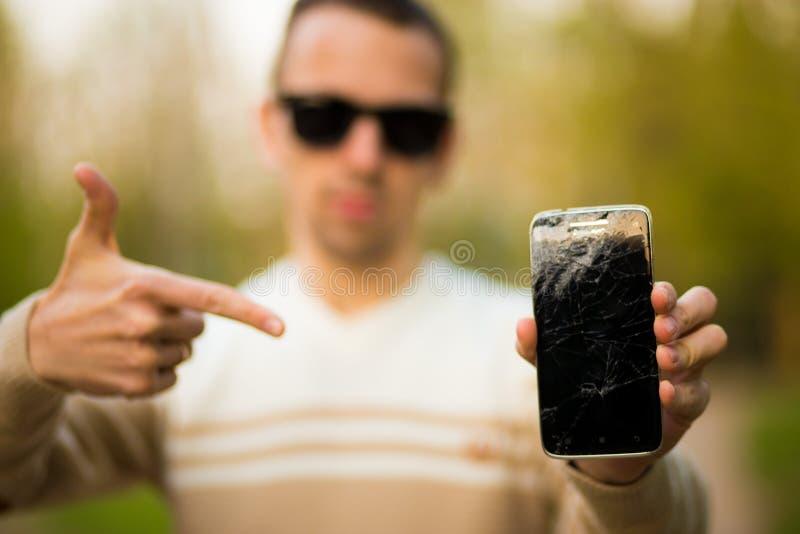 Indivíduo que guarda exposição quebrada do smartphone preto Tela quebrada do telefone frameless moderno o indivíduo que grita com imagem de stock