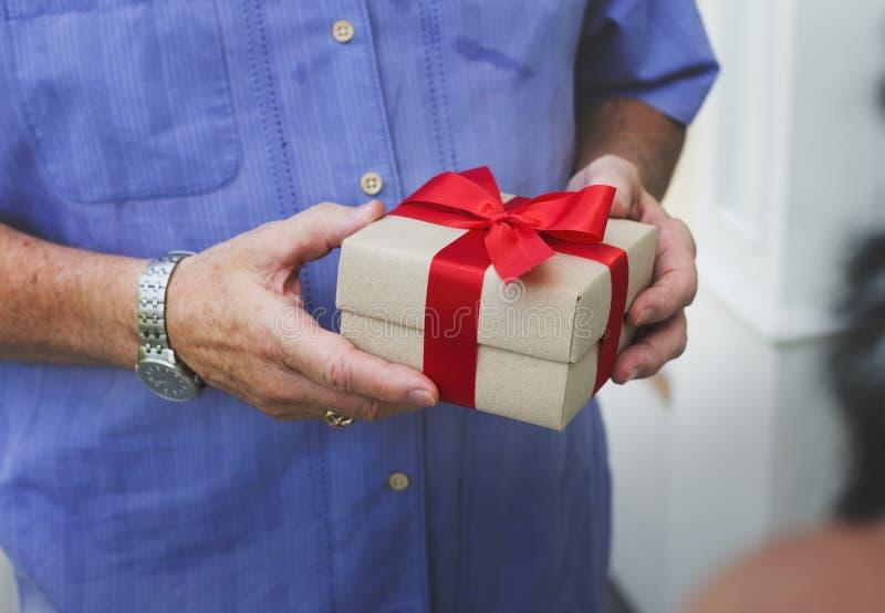 Indivíduo que guarda uma caixa do presente com curva vermelha foto de stock royalty free