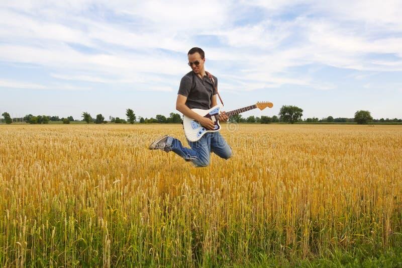 Indivíduo que joga a guitarra elétrica no campo de trigo imagens de stock royalty free
