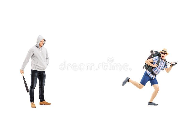 Indivíduo que mantém um bastão de beisebol e um turista assustado que tentam correr afastado fotografia de stock