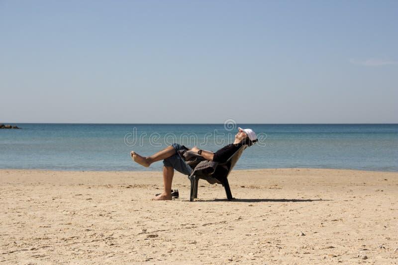 Indivíduo que relaxa em uma cadeira na praia foto de stock royalty free