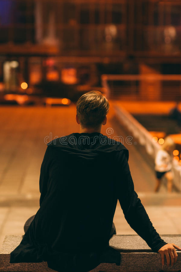 Indivíduo que senta-se na rua da noite, vista traseira foto de stock royalty free