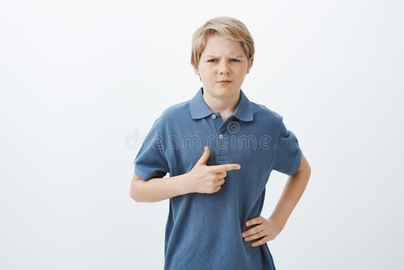 Indivíduo que sente incerto sobre o menino do ao lado Retrato da criança duvidosa suspeito com cabelo louro, guardando a mão sobr fotos de stock