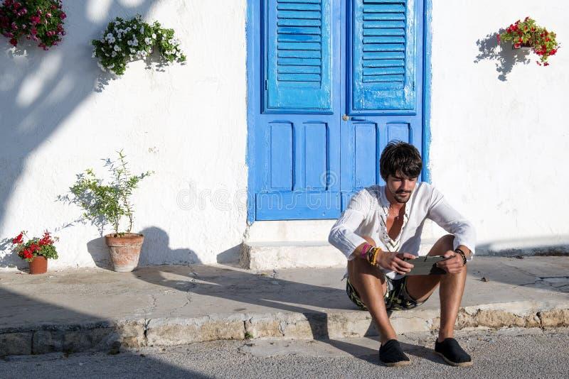 Indivíduo que trabalha na tabuleta em uma vila mediterrânea fotos de stock royalty free