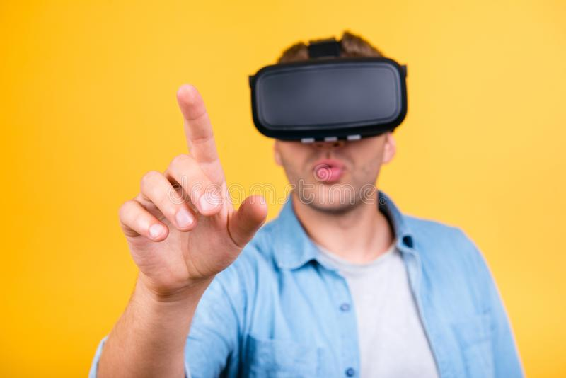 Indivíduo surpreendido na camisa das calças de brim que veste óculos de proteção da realidade virtual, usando-se foto de stock royalty free