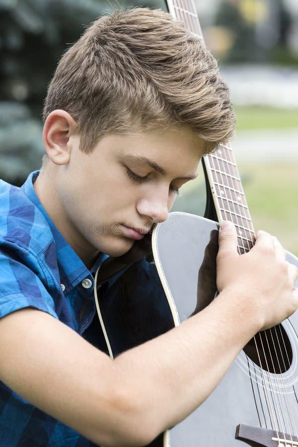 Indivíduo triste novo com uma guitarra fotos de stock royalty free