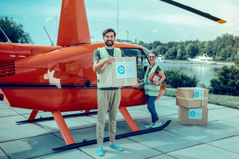 Indivíduos alegres positivos que são voluntários e caixas de coleta experientes com ajuda imagem de stock