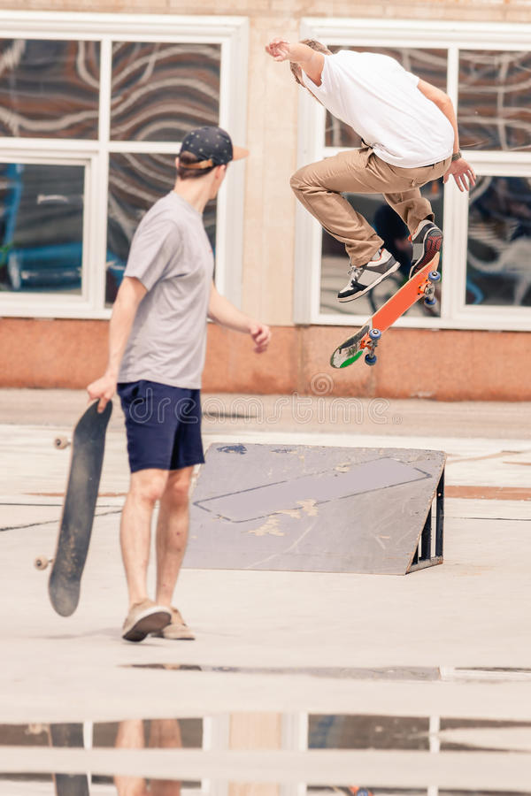 Indivíduos consideráveis que montam e que fazem o truque pelo skate imagem de stock