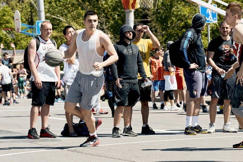 Indivíduos novos que jogam o basquetebol na rua na cidade fotografia de stock