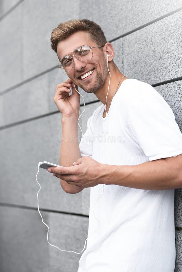 Indiv?duo alegre vestido no t-shirt branco na rua, escutando a m?sica com os fones de ouvido, guardando o telefone celular fotos de stock