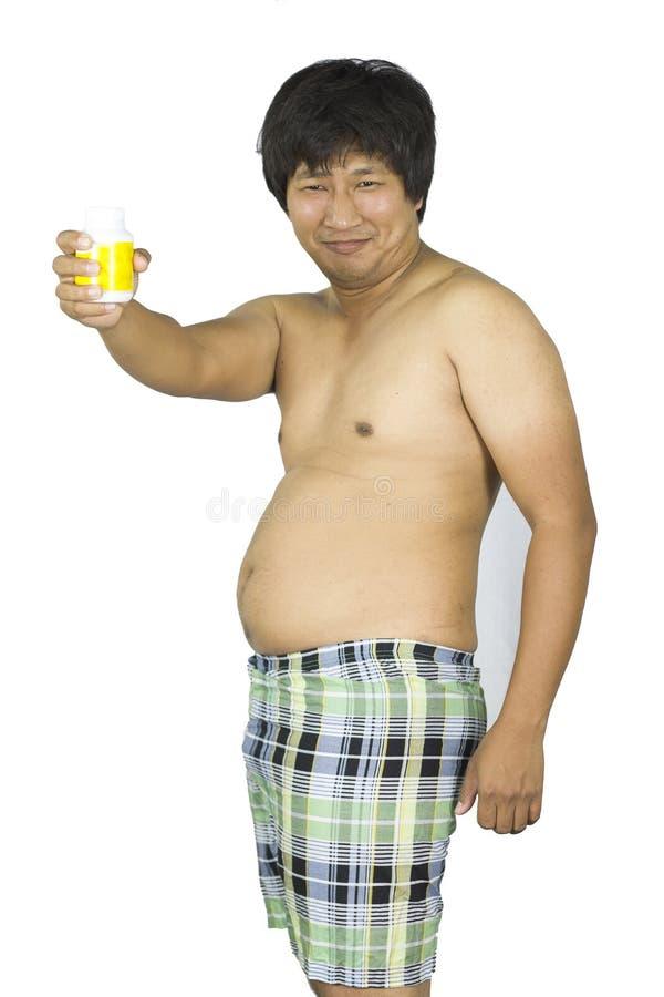 Indiv?duo gordo que guarda um frasco amarelo dos comprimidos no fundo isolado branco no est?dio imagens de stock royalty free