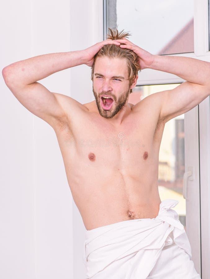Indiv?duo muscular 'sexy' macho do torso que relaxa perto do quarto da janela Conceito da sa?de e do bem estar Sentimento bom Man fotografia de stock