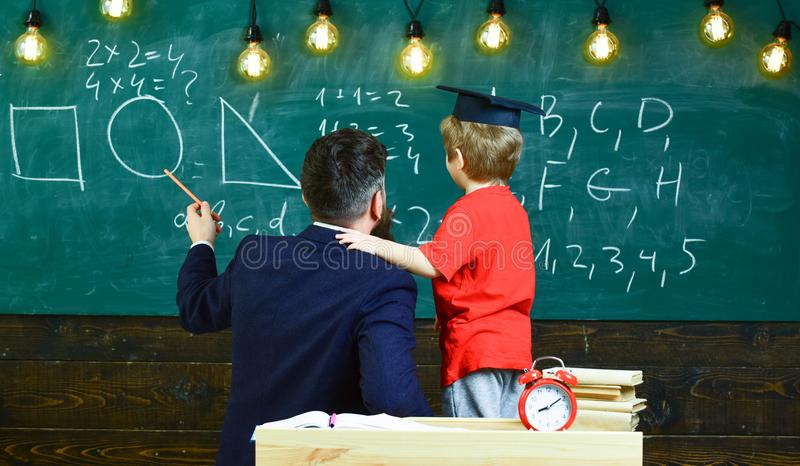 Individual education concept. Teacher and schoolboy turned back in classroom. Kid in graduation cap holding adult male stock images