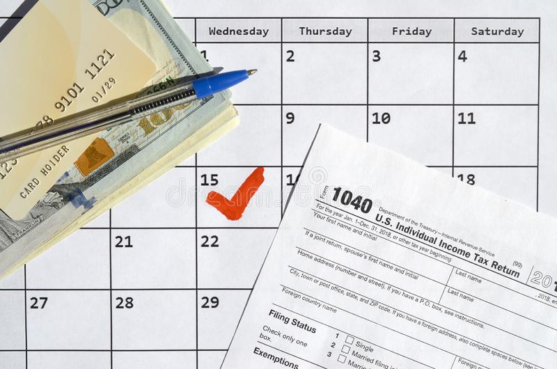 1040 Individual Income Tax Return blank with credit card on dollar bills and pen on calendar page with marked 15th April. Tax period concept. IRS Internal royalty free stock image
