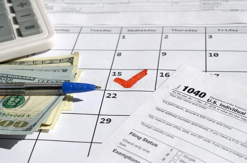 1040 Individual Income Tax Return blank with dollar bills, calculator and pen on calendar page with marked 15th April. Tax period concept. IRS Internal Revenue royalty free stock images