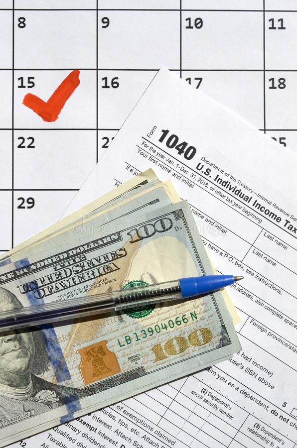 1040 Individual Income Tax Return blank with dollar bills, calculator and pen on calendar page with marked 15th April. Tax period concept. IRS Internal Revenue stock photo