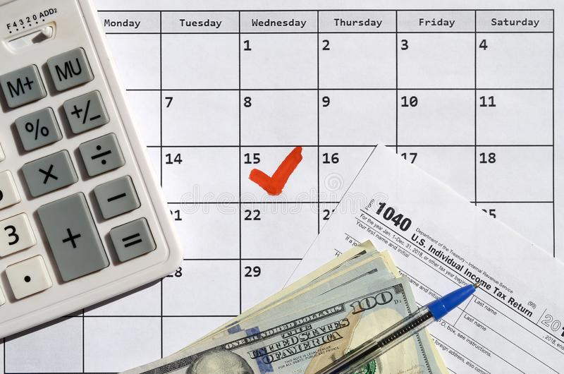 1040 Individual Income Tax Return blank with dollar bills, calculator and pen on calendar page with marked 15th April. Tax period concept. IRS Internal Revenue royalty free stock photo