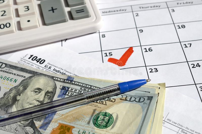 1040 Individual Income Tax Return blank with dollar bills, calculator and pen on calendar page with marked 15th April. Tax period concept. IRS Internal Revenue stock images