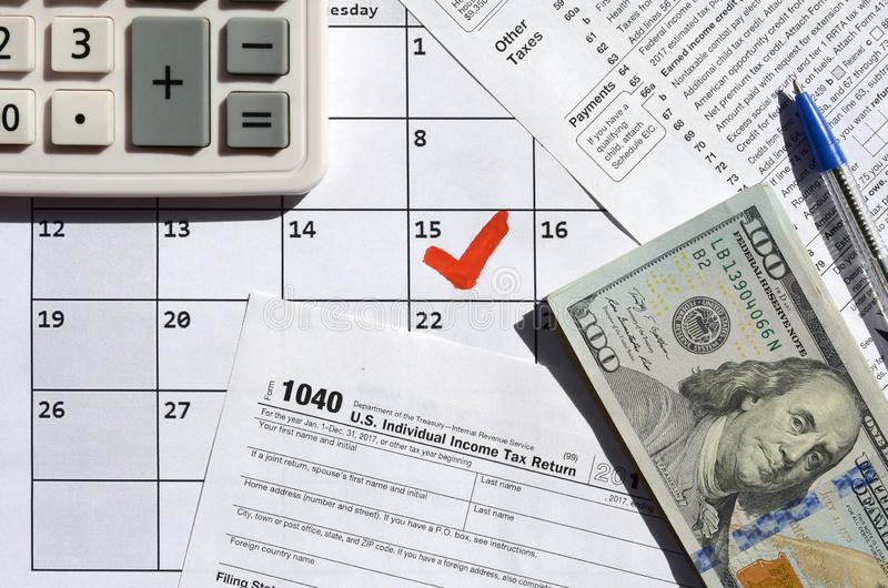 1040 Individual Income Tax Return blank with dollar bills, calculator and pen on calendar page with marked 15th April. Tax period concept. IRS Internal Revenue stock image