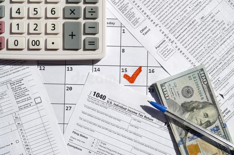 1040 Individual Income Tax Return blank with dollar bills, calculator and pen on calendar page with marked 15th April. Tax period concept. IRS Internal Revenue royalty free stock photos
