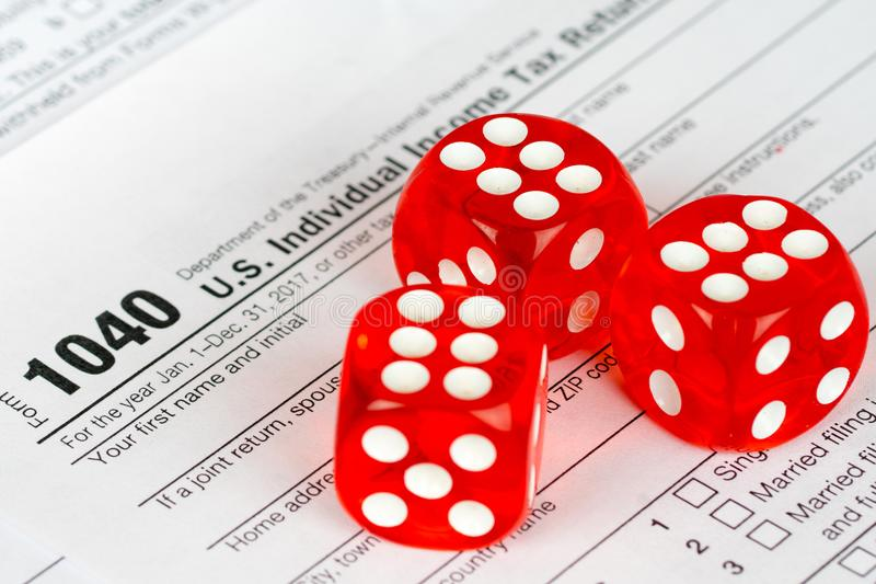 Tax return form 1040 with three red dices stock photos