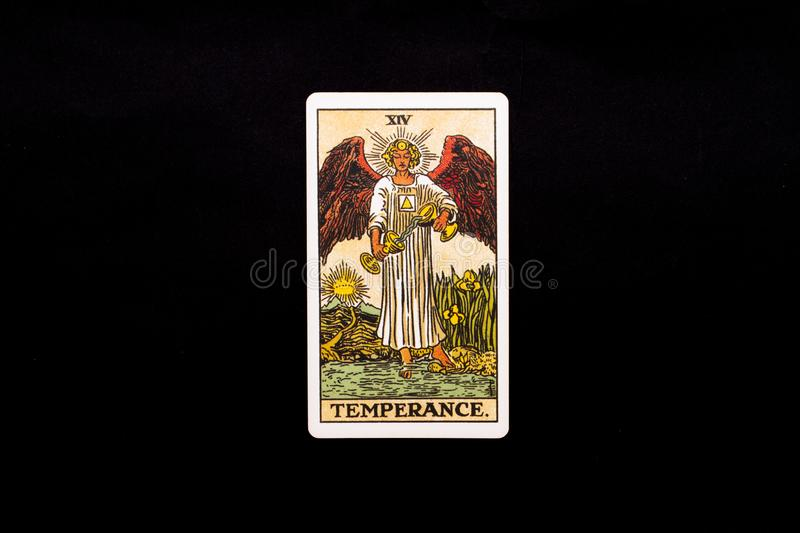 An individual major arcana tarot card isolated on black background. Temperance. Rider Waite tarot deck. Good to use as a background, or an isolated object stock image