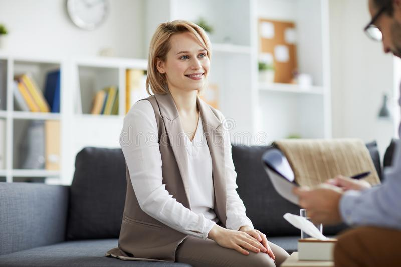 Individual session. Happy young casual women looking at her counselor while listening to his advice during individual session stock image