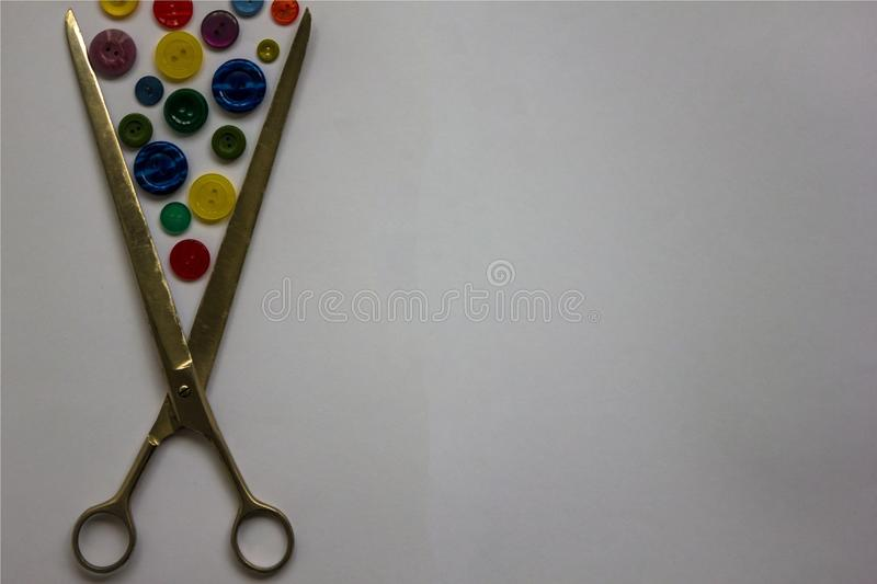 Individual tailoring. Scissors for cutting fabrics and various buttons for clothes. Sewing accessories, home hobby. View from above. Light background stock images