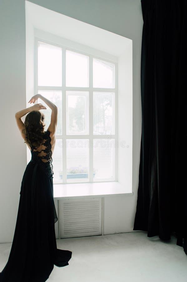 individualiteit Nadenkende Elegante Dame in Zwarte Prom-Avondjurk stock afbeeldingen