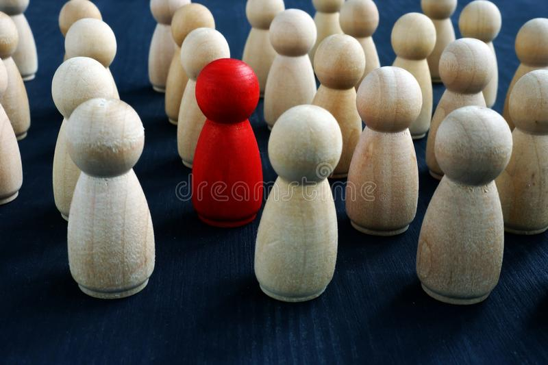 Individuality, personality and originality concept. Red wooden figure in crowd. Individuality, personality and originality concept. Red wooden figure in the stock photography