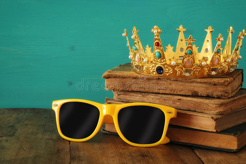 Individuality and unique concept. Old medieval gold crown and cool sunglasses royalty free stock images