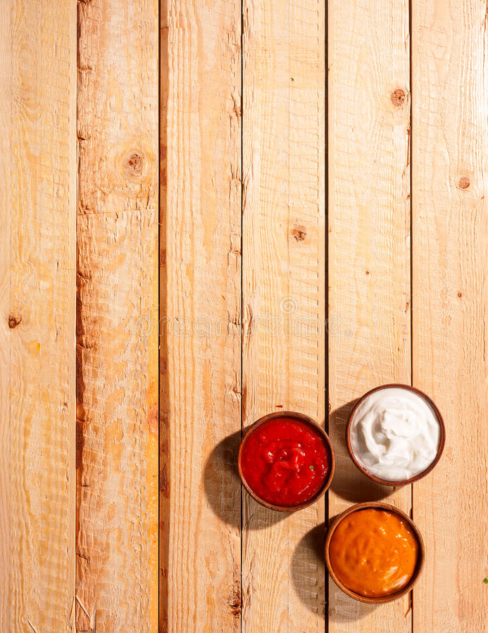 Individuals sauces for a summer barbecue. Standing ready on a wooden picnic table outdoors with tomato ketchup, mayonnaise and spicy mustard, overhead view stock photo