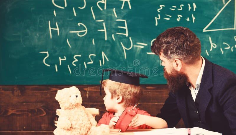 Individueel lessenconcept De jongen, kind in gediplomeerd GLB bekijkt gekrabbel op bord terwijl de leraar verklaart leraar stock fotografie