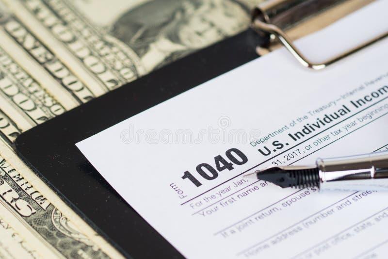 Individuell inkomstskattåtergångform 1040 med dollar royaltyfria foton