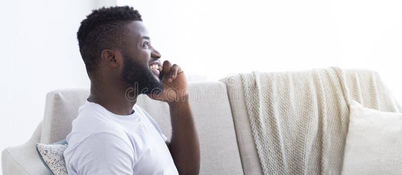 Individuo africano alegre que disfruta de charla del teléfono en casa, vista lateral foto de archivo libre de regalías