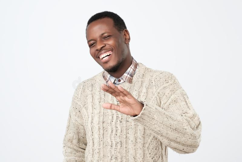 Individuo africano de risa vestido en el gesto caliente de la parada de la demostración del suéter, pidiendo parar el bromear, co imagen de archivo libre de regalías