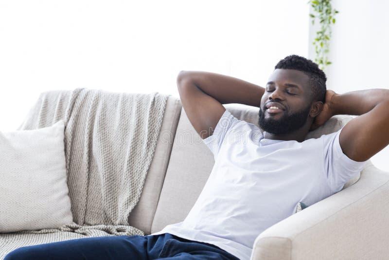 Individuo africano feliz que se relaja en casa, sentándose en el sofá con los ojos cerrados imagen de archivo libre de regalías