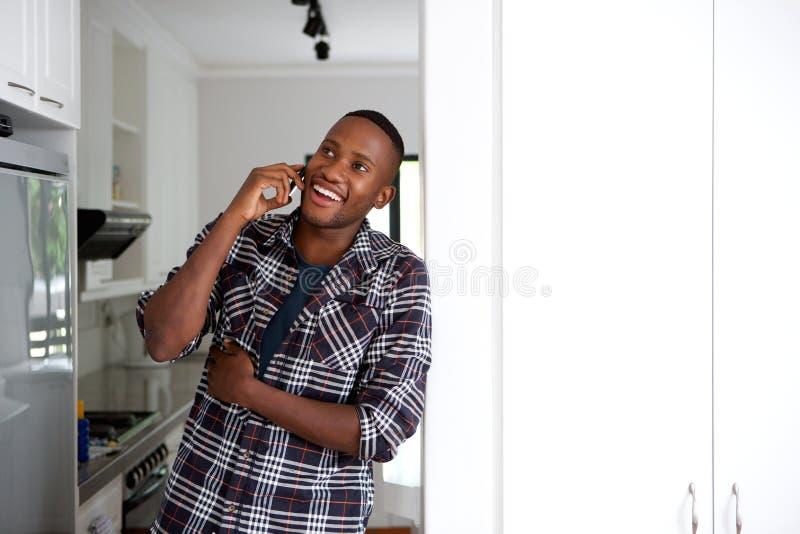 Individuo africano joven feliz en casa que hace una llamada de teléfono imagen de archivo