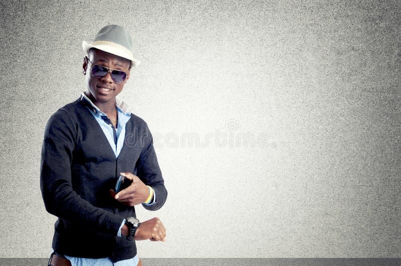 Individuo africano joven que mira a que hora es imagenes de archivo