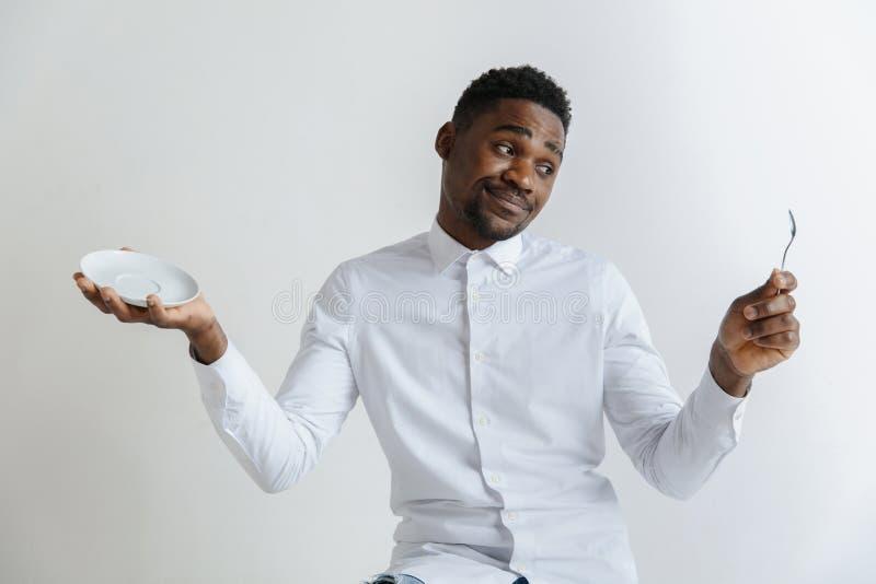Individuo afroamericano atractivo que duda joven que sostiene el plato vacío y cuchara aislada en fondo gris Copie el espacio y imagen de archivo
