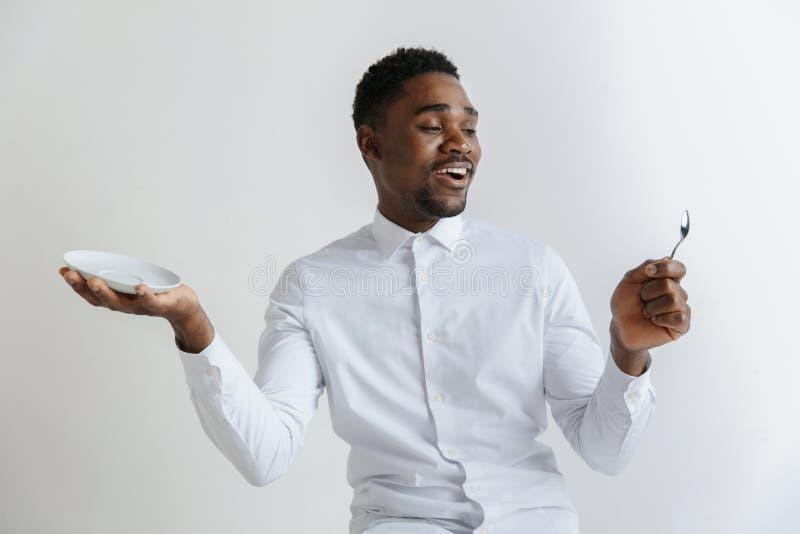 Individuo afroamericano atractivo sonriente joven que sostiene el plato vacío y cuchara aislada en fondo gris imagen de archivo libre de regalías
