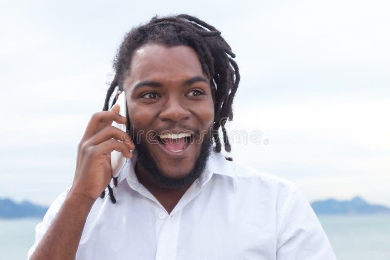 Individuo afroamericano de risa con los dreadlocks y camisa blanca en el teléfono fotos de archivo libres de regalías
