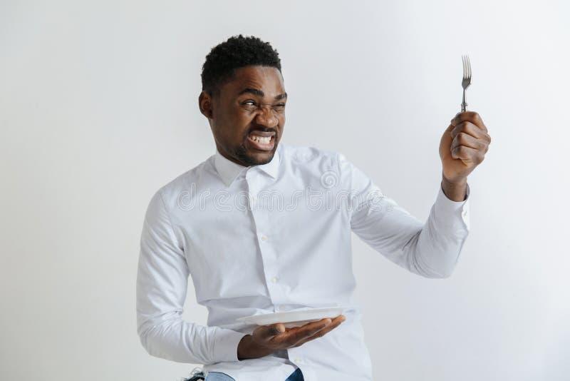 Individuo afroamericano joven que sostiene el plato vacío y la bifurcación con el disgusto de la expresión facial aislados en fon fotos de archivo