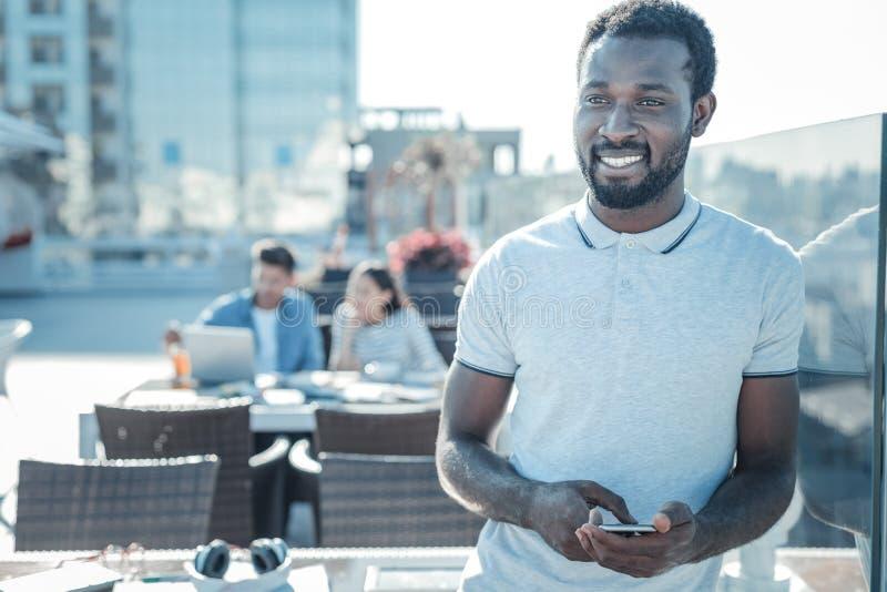 Individuo afroamericano pensativo con smartphone que sueña y que sonríe imágenes de archivo libres de regalías