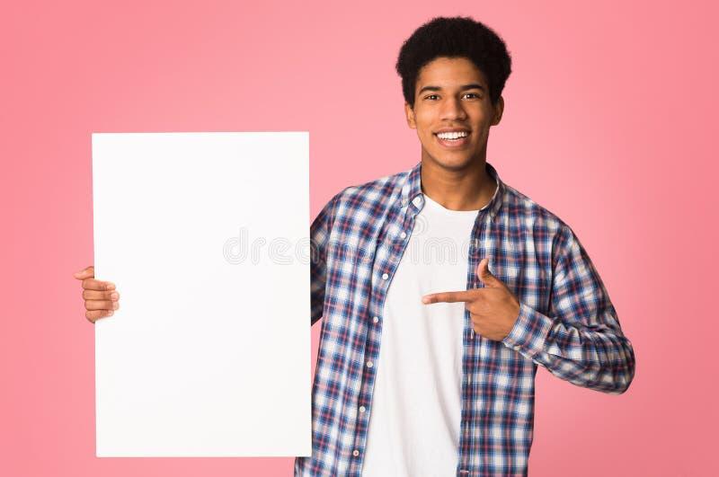 Individuo afroamericano que señala en la bandera en blanco, fondo rosado fotografía de archivo libre de regalías