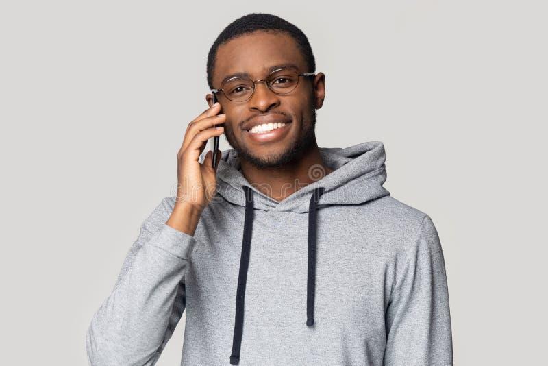 Individuo afroamericano sonriente en charla de la sudadera con capucha sobre el teléfono móvil fotos de archivo libres de regalías