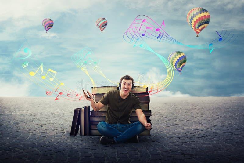 Individuo alegre del estudiante asentado relajado en el piso que escucha una canción en los auriculares fotos de archivo