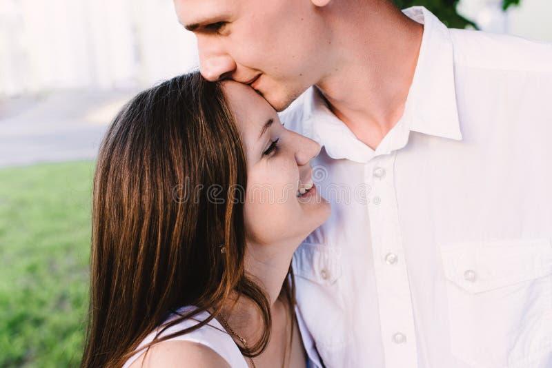 Individuo alegre que se besa la frente de risa de las muchachas suavemente fotos de archivo libres de regalías