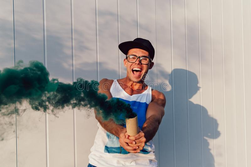 Individuo alegre que se divierte al aire libre, mientras que juega con la bomba de humo imagenes de archivo