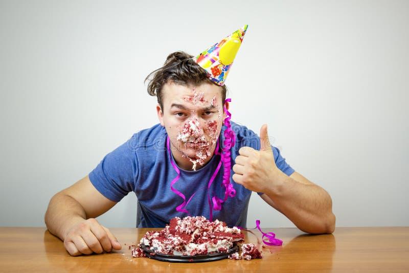 Individuo apuesto infeliz del cumpleaños del retrato con la torta en el pulgar de la demostración de la cara para arriba, infeliz fotos de archivo libres de regalías